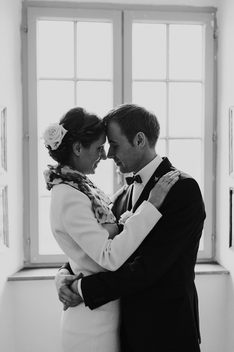 Brautpaar steht am Fenster im Schloss