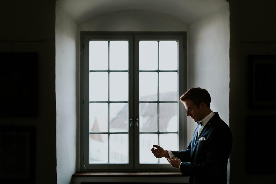 Braeutigam macht sich am Fenster im Schloss zurecht