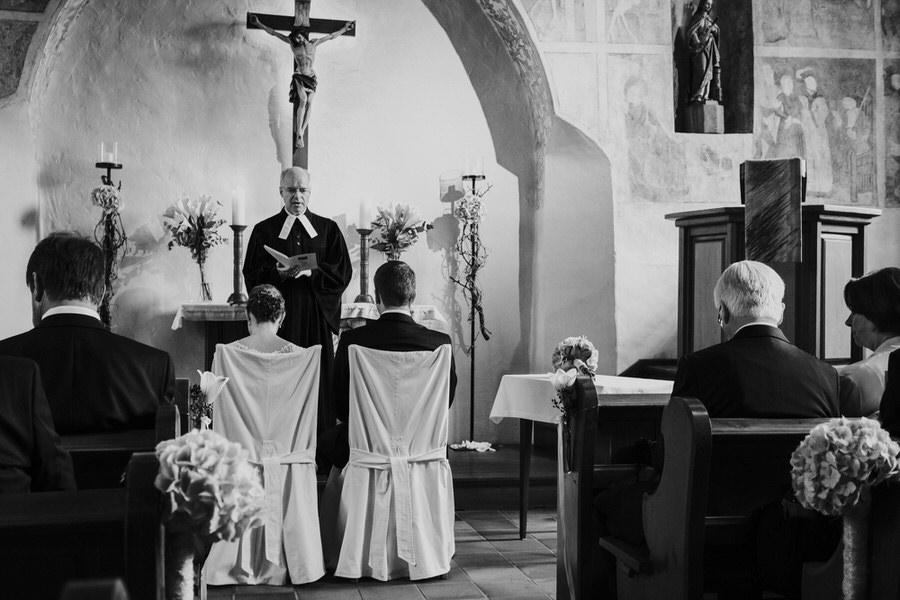 Pfarrer steht vor dem Brautpaar  während der Trauung