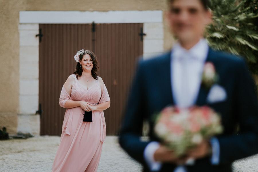 Braut steht hinter dem Braeutigam beim First Look Moment