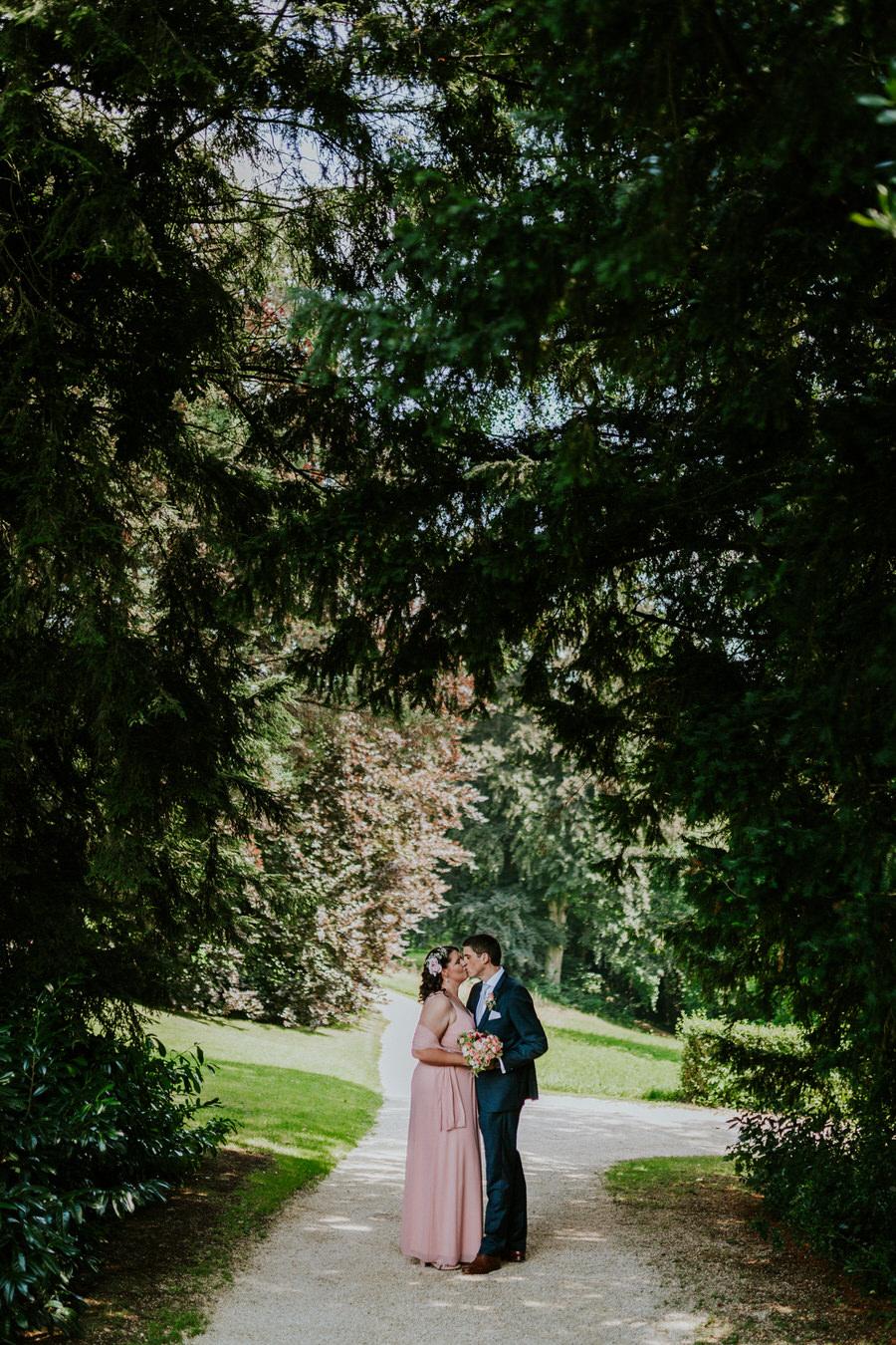 Brautpaar steht im Grünen im Park des Schloss Fachsenfeld