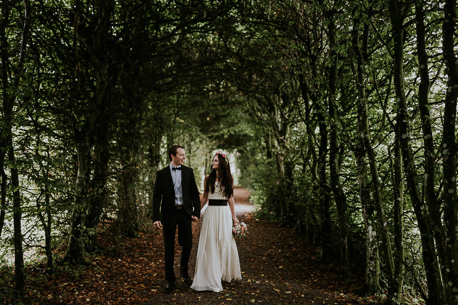 A couple walking in woods after the wedding.