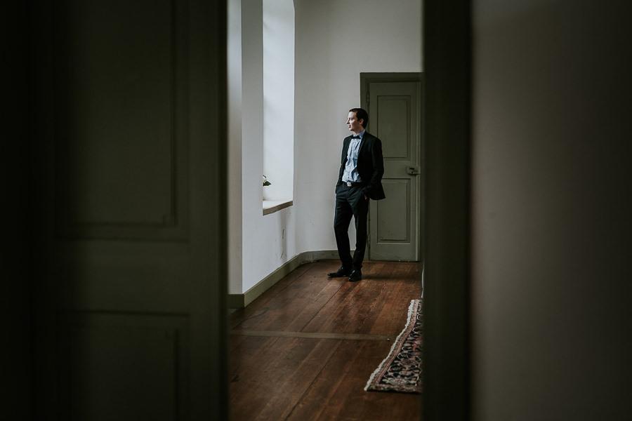 Bräutigam steht vor dem Fenster im Lusthaus in Abtsgmünd