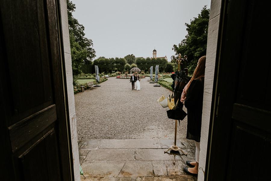 Braut mit Bräutigam geht zur Trauung beim Regen auf Schloss Hohenstadt mit Hochzetisfotografin Anastasia Vyatkina