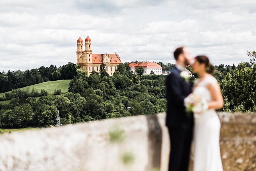 brautpaar steht auf Schloss Ellwangen mit der Aussicht auf Schönenbergkirche