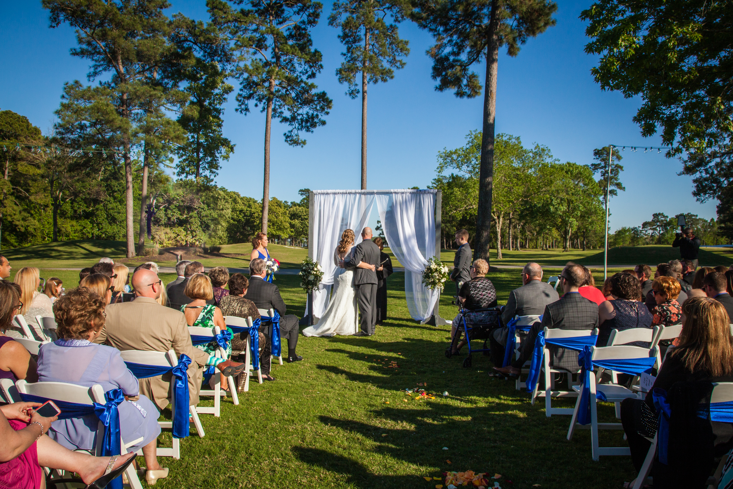 Beautiful wedding with clear blue skies and green grass at the Kingwood venue.