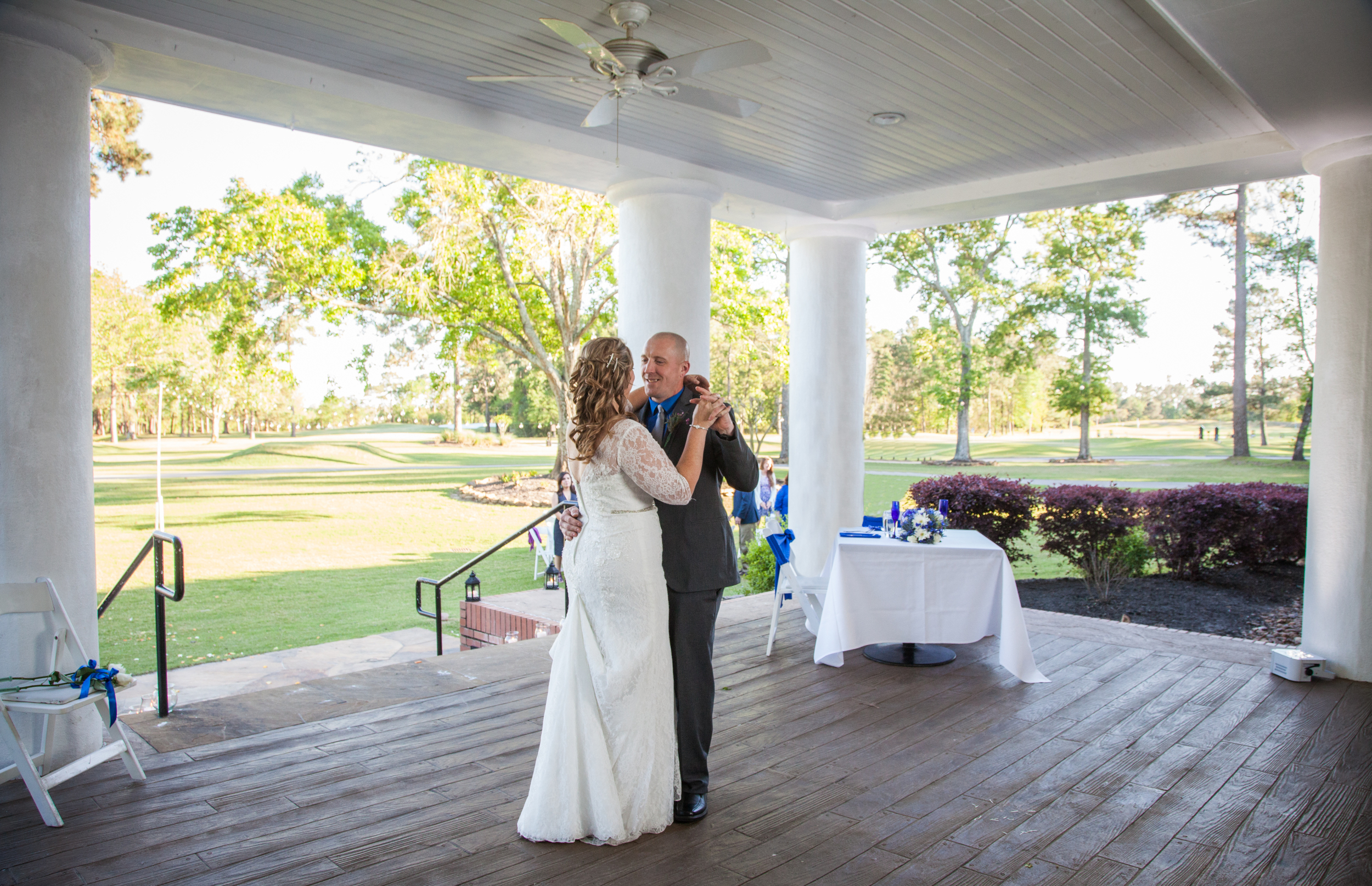 The couple dance for the first time together on the dance floor as husband and wife. The golf course is beautifully lit in the background as the sun sets.