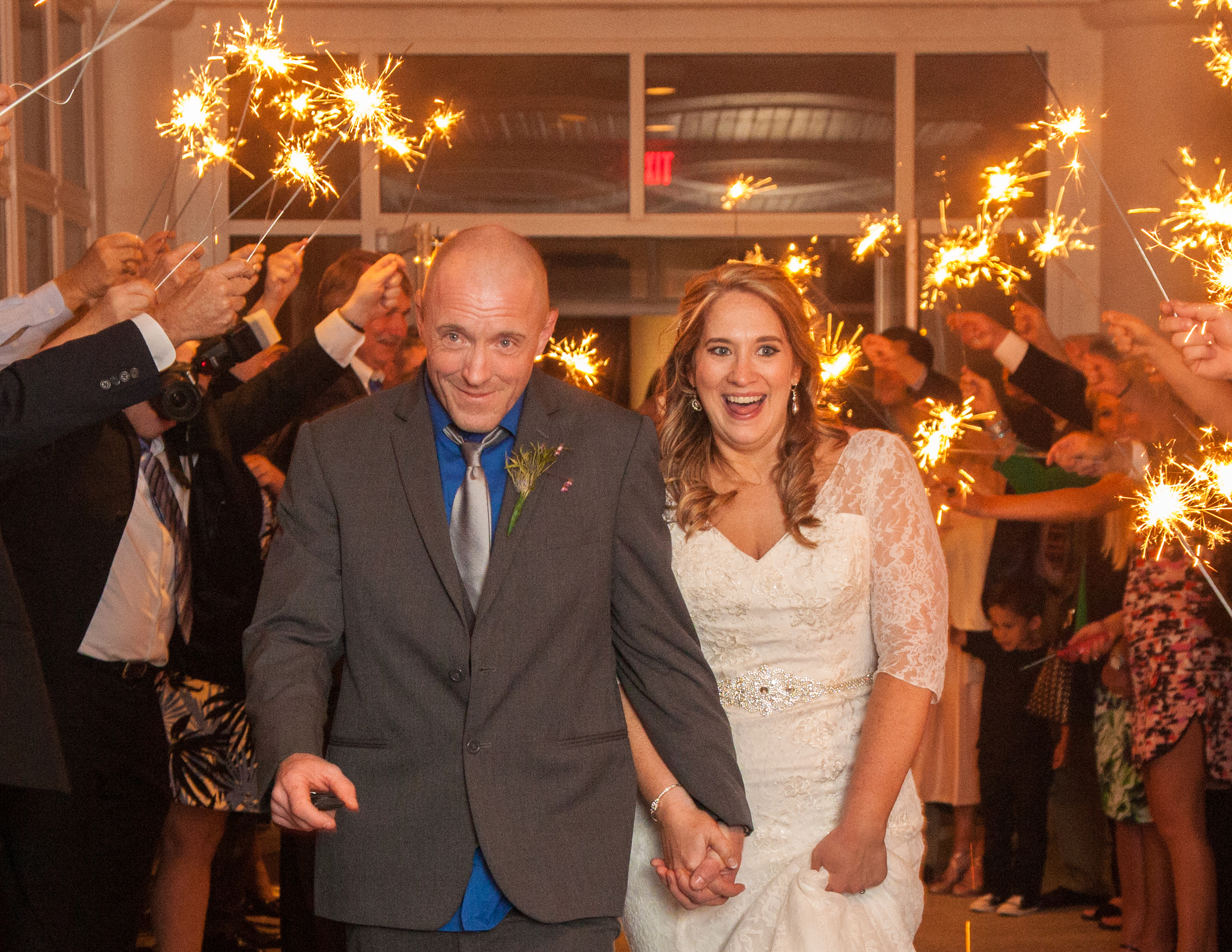 Husband and wife make their grand exit through a tunnel of sparklers leading to their getaway car.