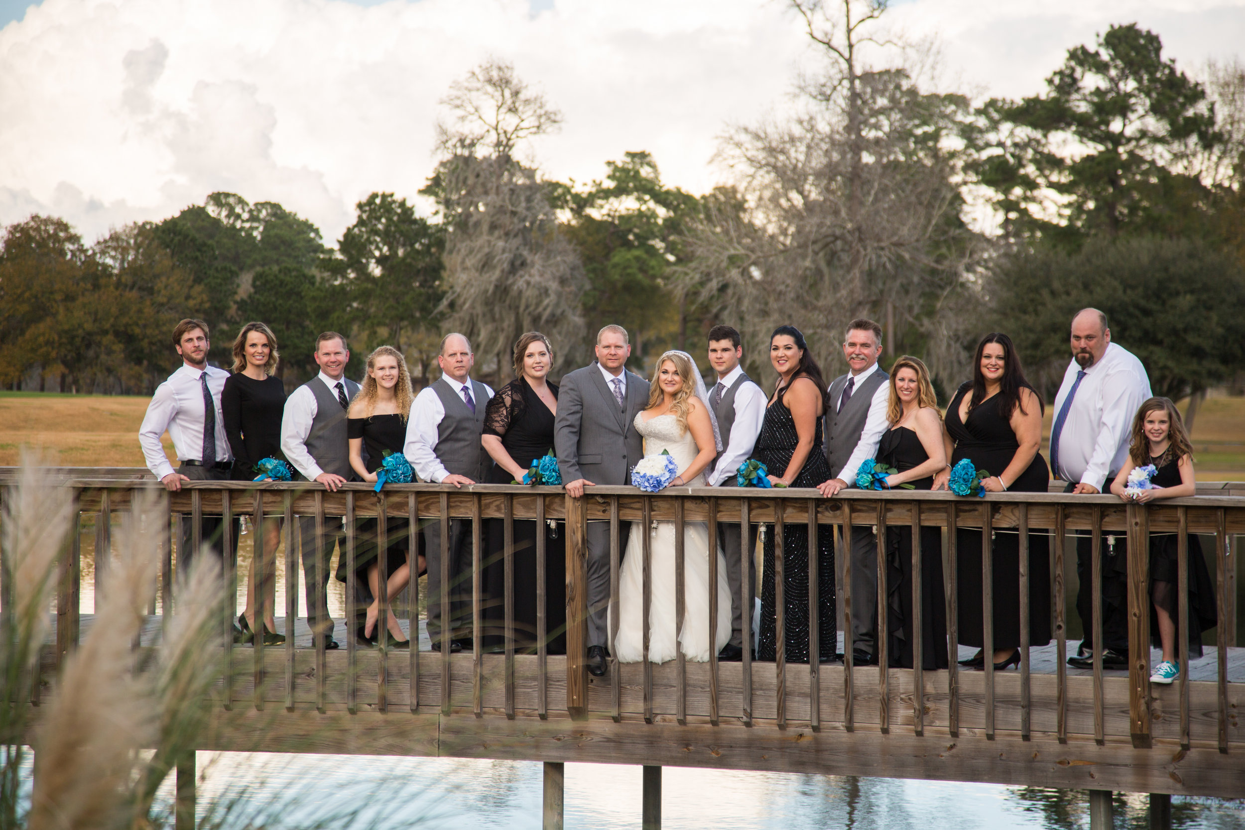Group portrait of the wedding party on a bridge at sunset.