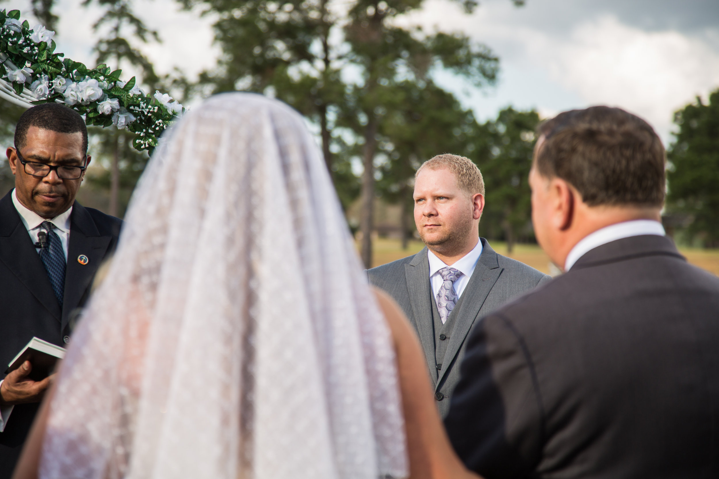 The groom Kennith looks on as bride Jessica stands with her father in wait before the minister asks him to give her away.