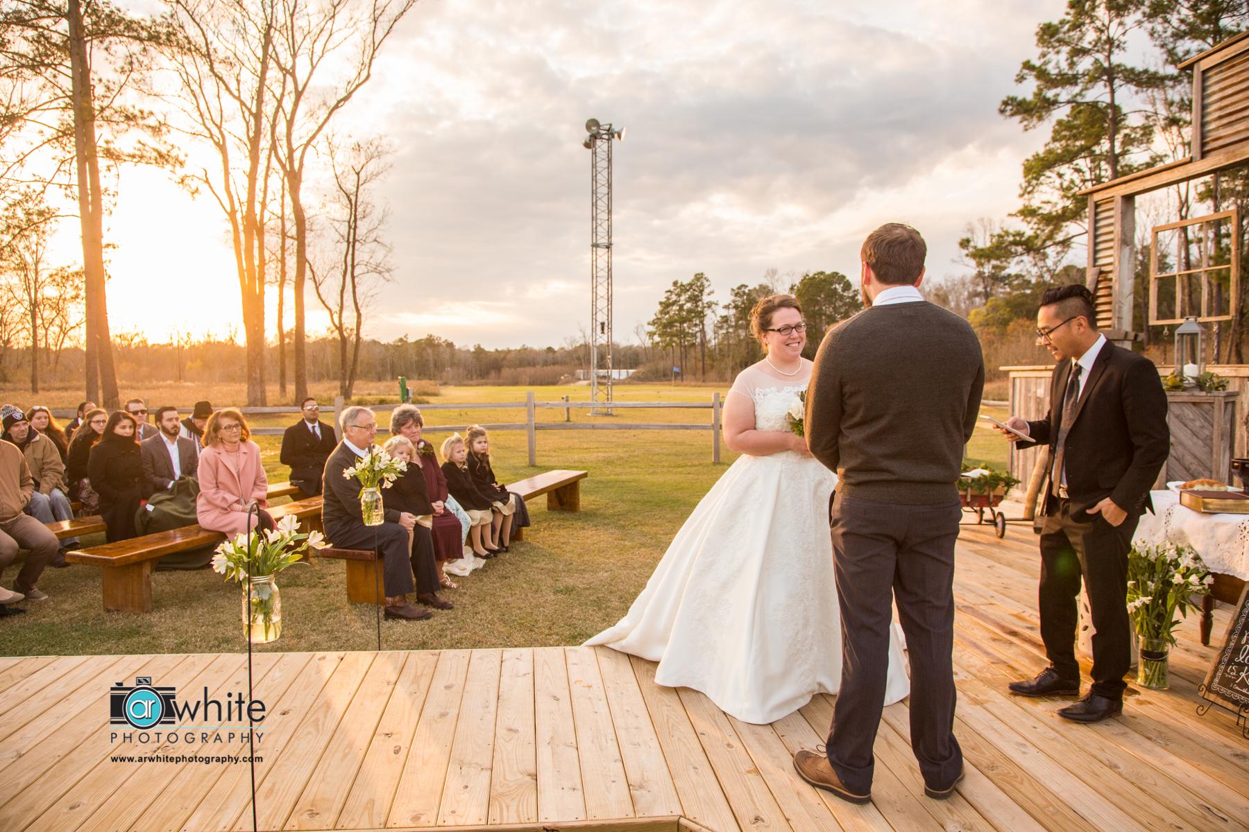 Barn wedding ceremony at sunset.