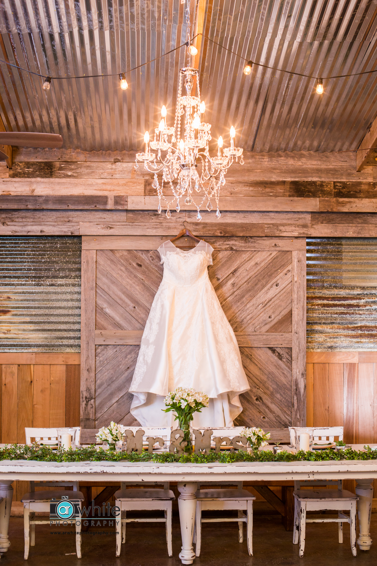 Wedding dress at a barn venue hung against a barn door with shabby chic chandelier and string lights in foreground.