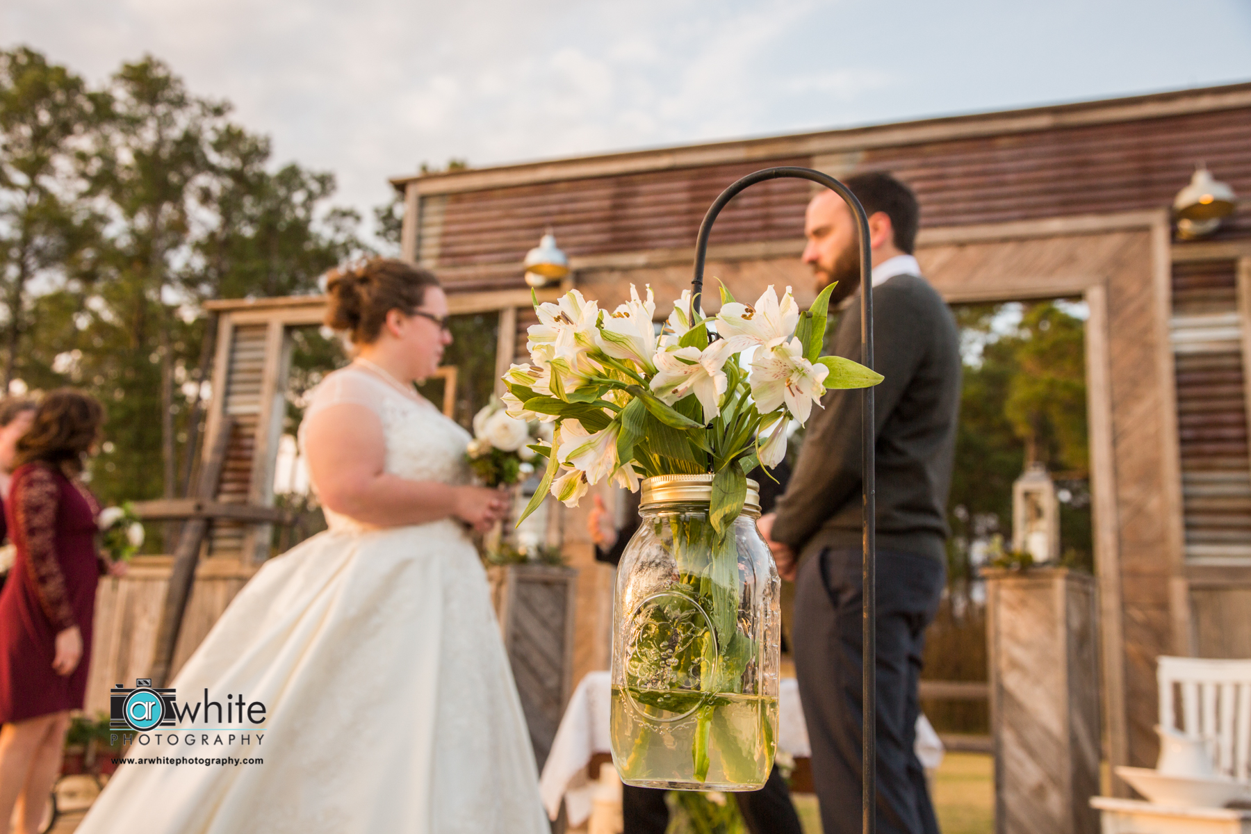 A mason jar with white flowers is used at a barn wedding for isle decoration at the alter.