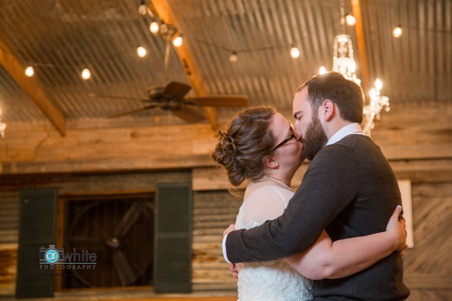 Husband and wife kiss after their first dance during the reception at a barn wedding.