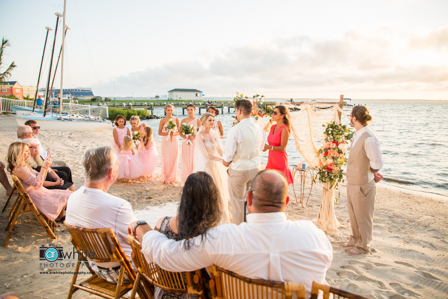 A couple recite their wedding vows on the beach at sunset.