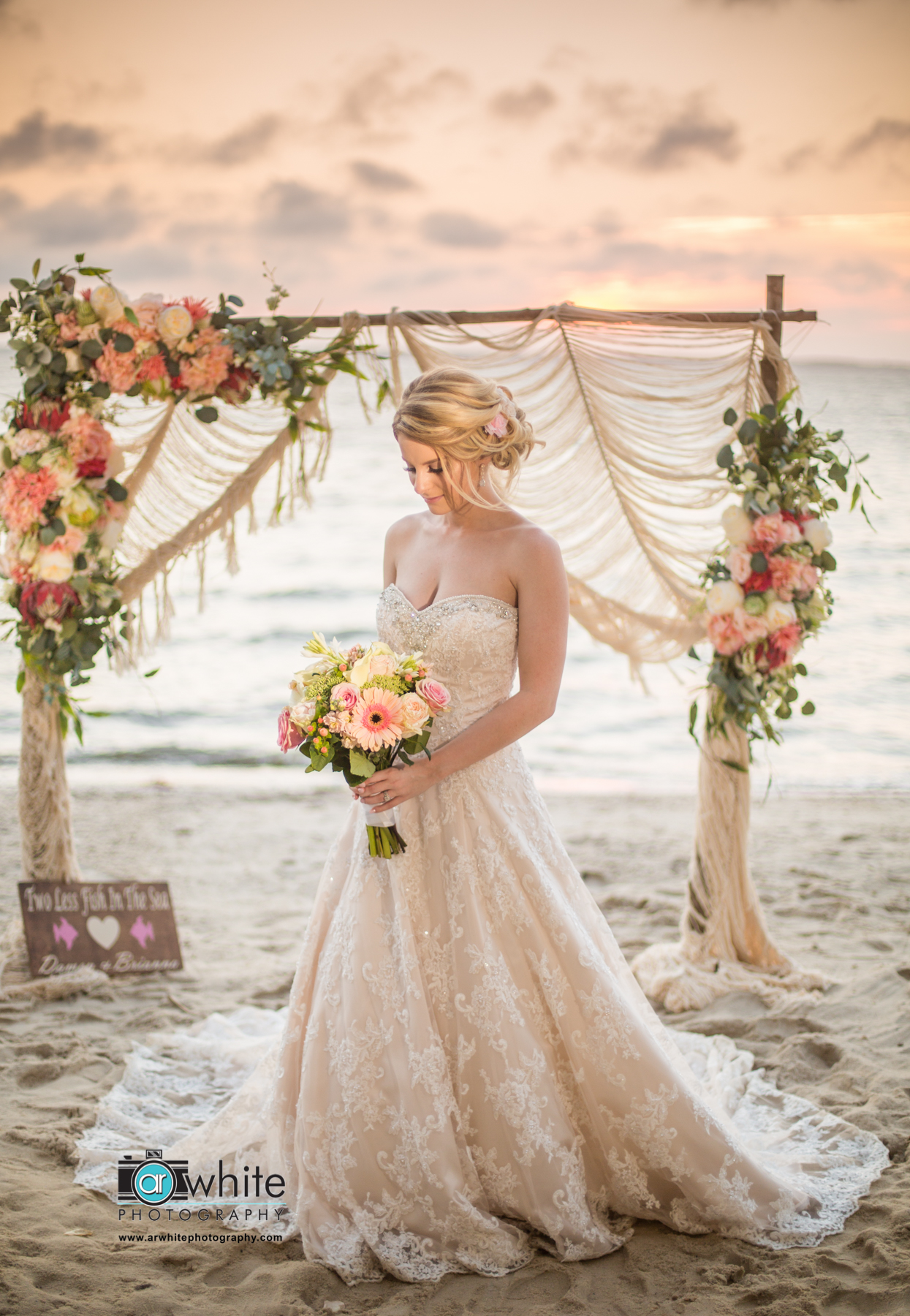 Brianna, bride holds her flower bouquet on the beach in front of the arbor after her Bohemian wedding in Oc Md.