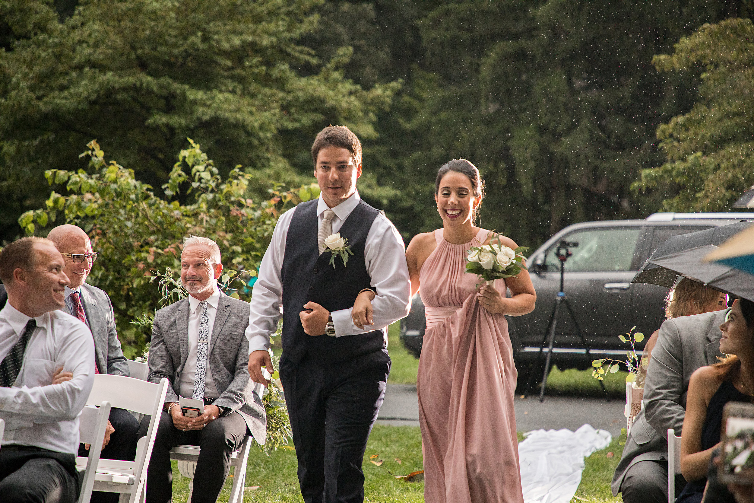 Rain falls as the maid of honor and best man walk down the isle.