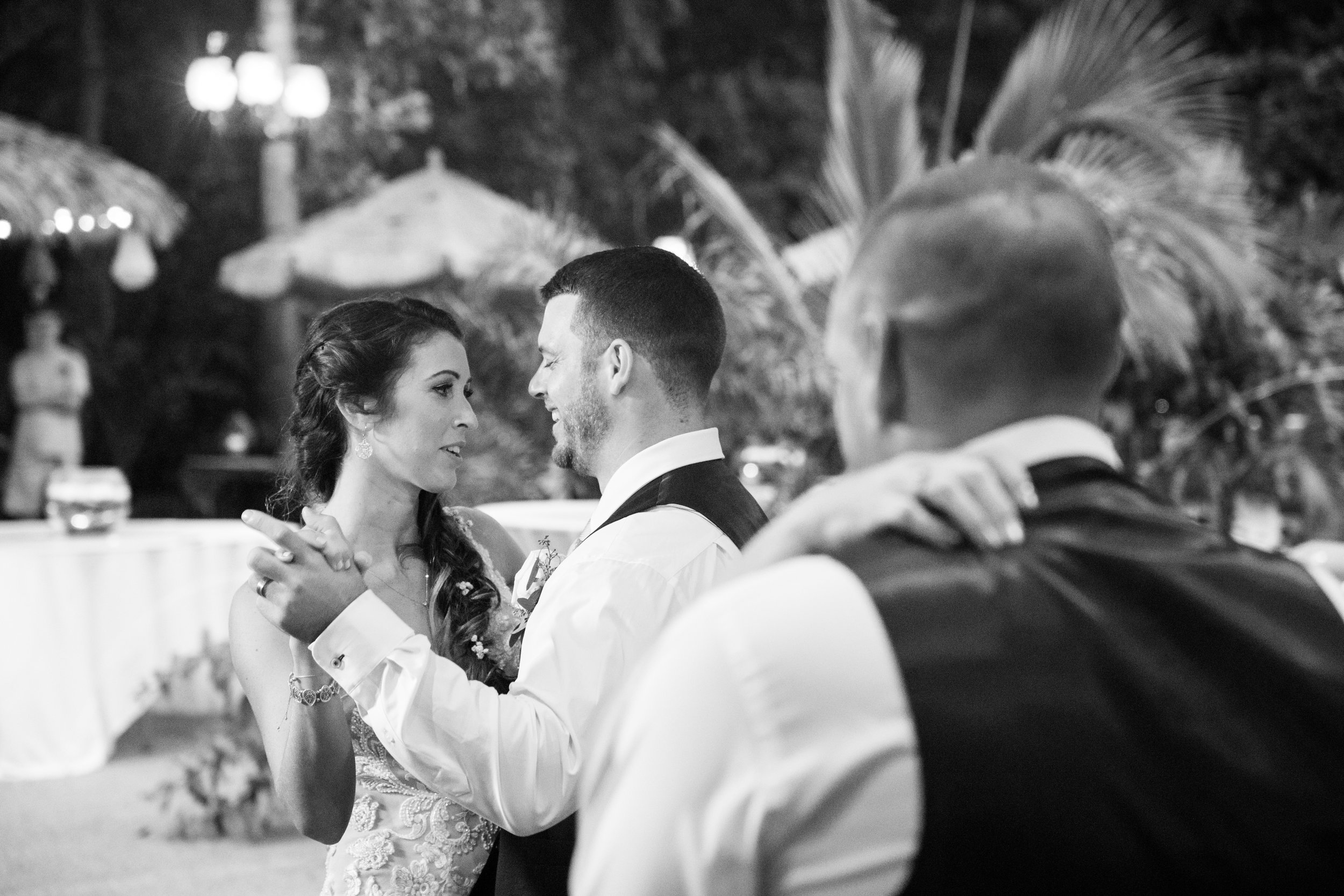 The couple share their first dance with other couple's on the dance floor.