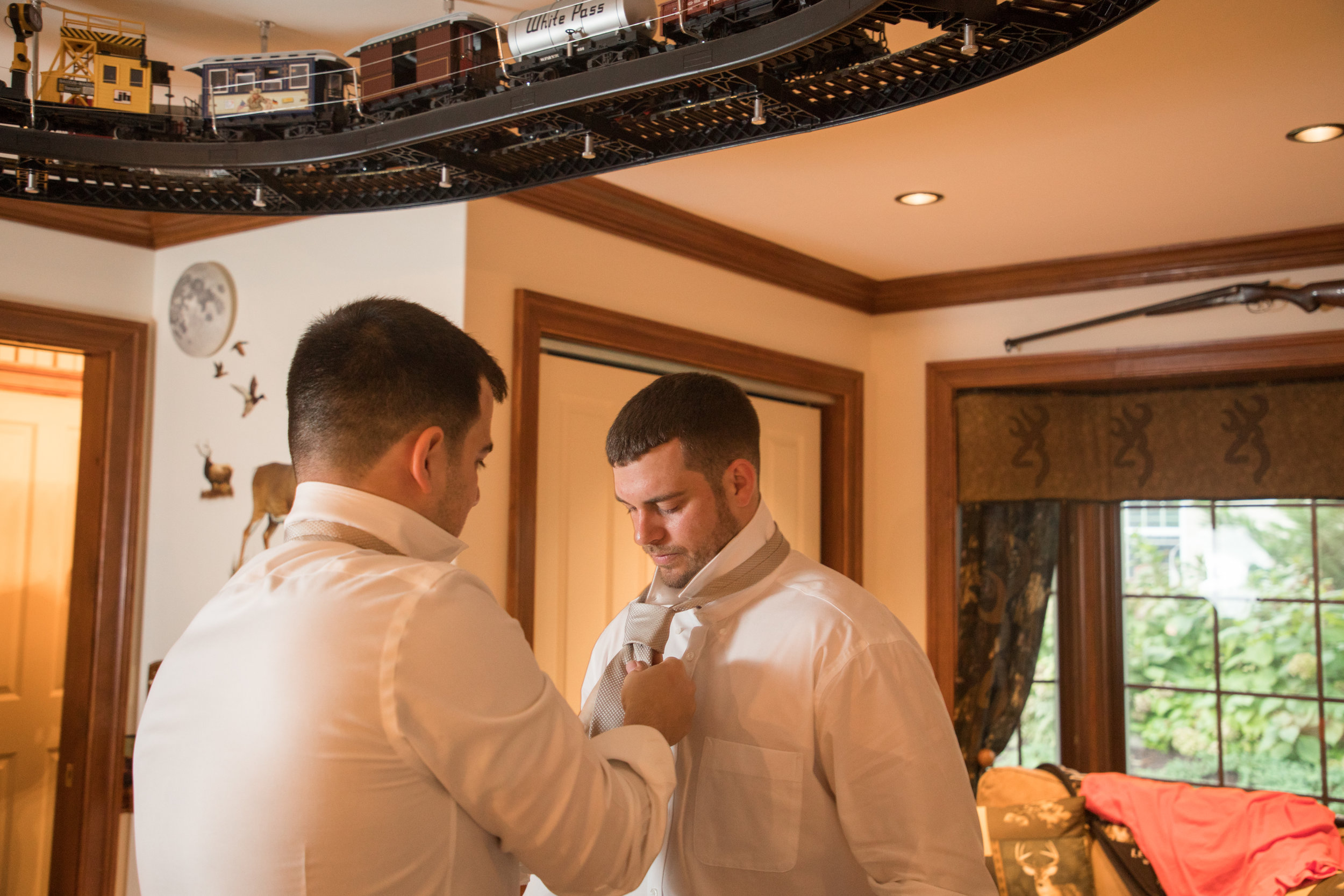 A groomsman fixes the groom's tie as they get ready before the start of the wedding ceremony in Milford Delaware.