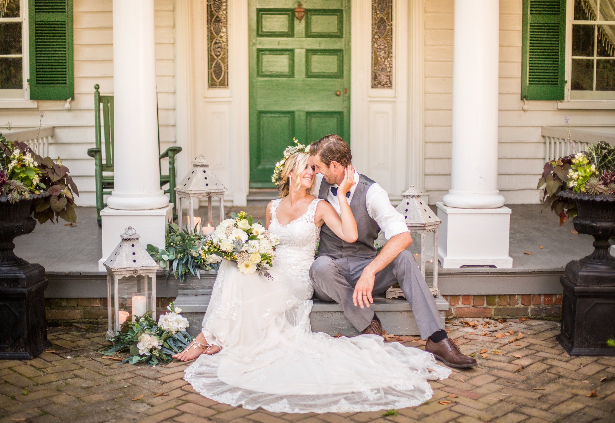 Bride and groom sit on the steps in front of a historic home in Berlin, Md.