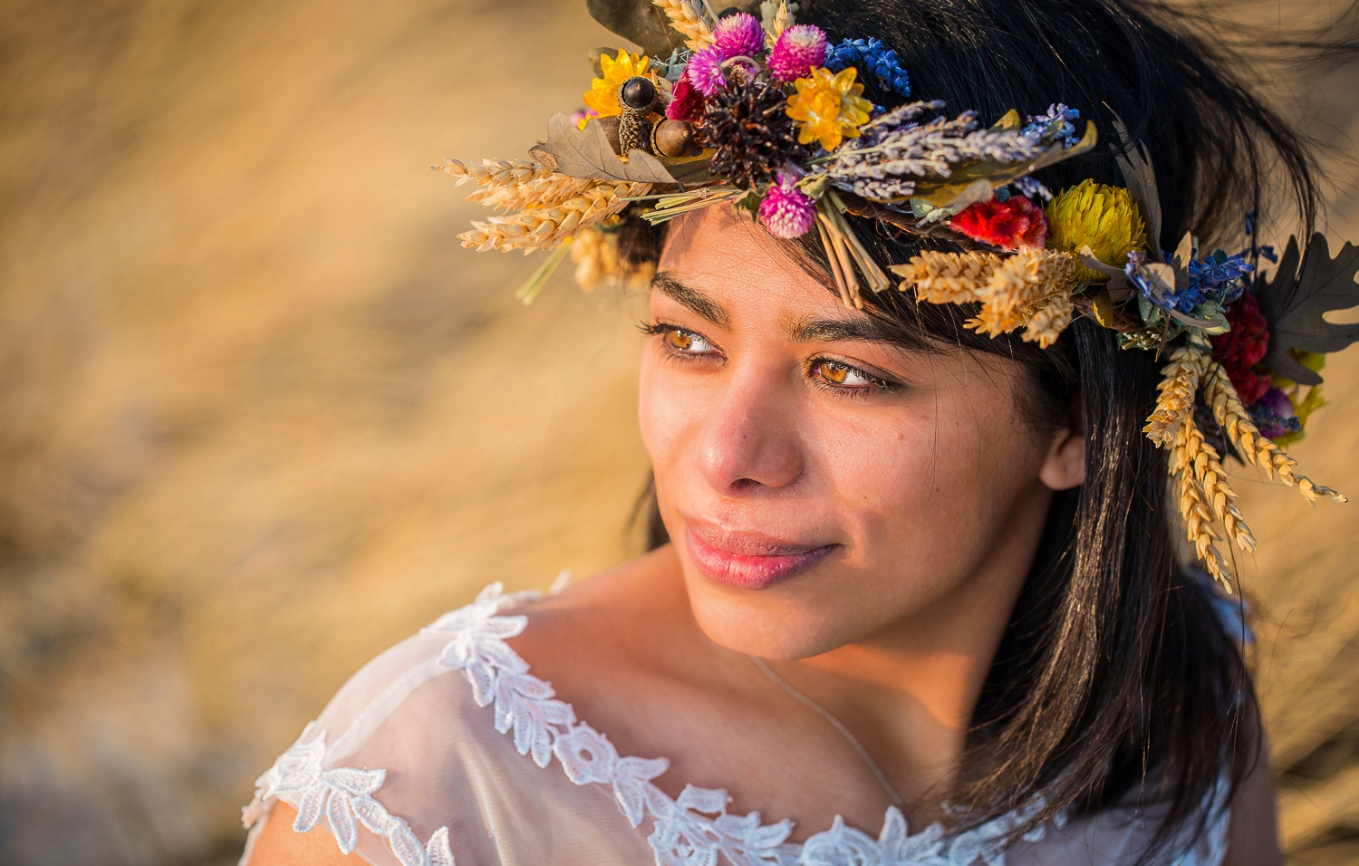A beautiful bride with a flower crown looks off into the sunset on her wedding day.