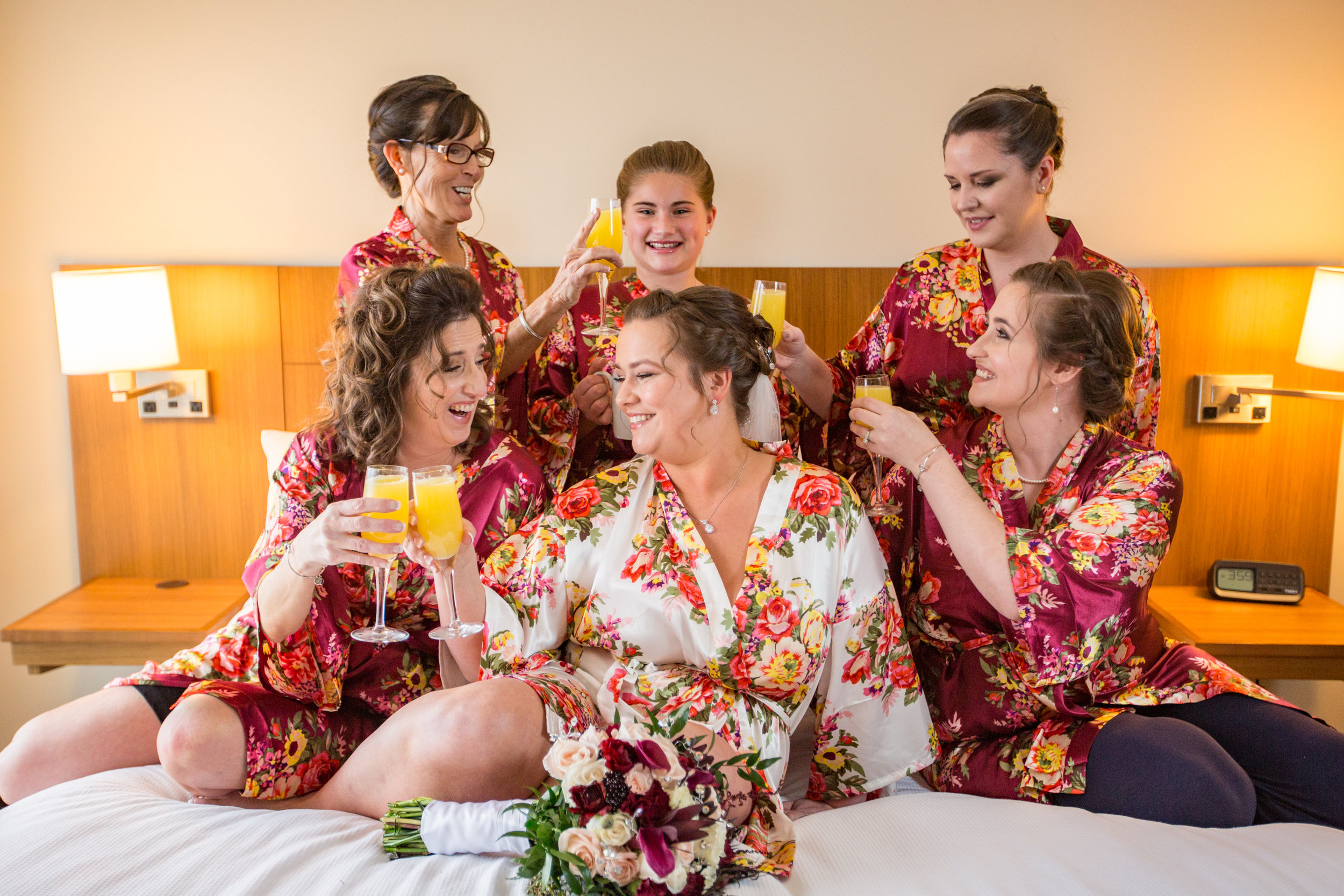 Jenna with her bridesmaids enjoy memosas in their gowns prior to getting ready for her big day in Ocean City, MD.