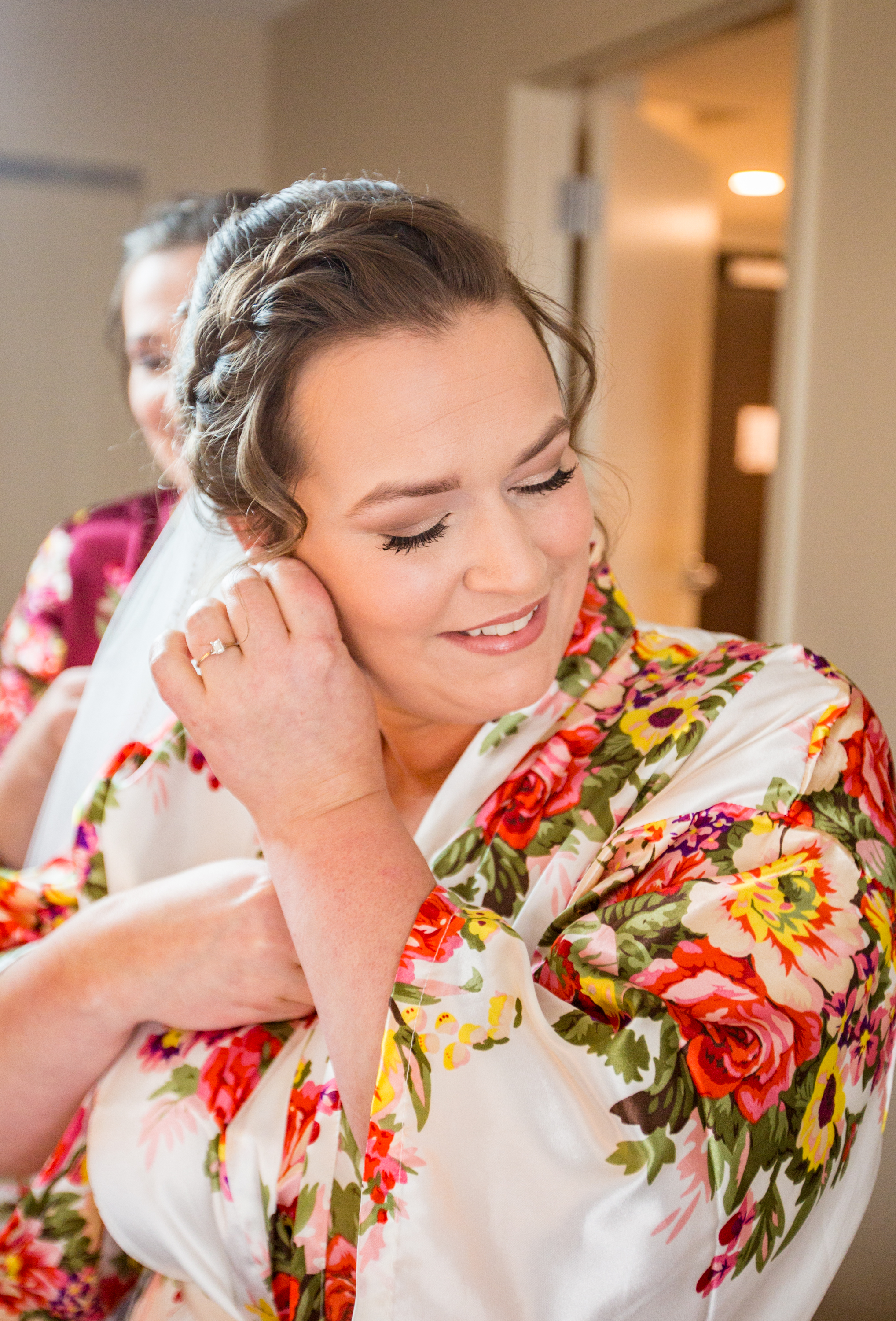 The bride puts her earrings in after getting her makeup done prior to her wedding.