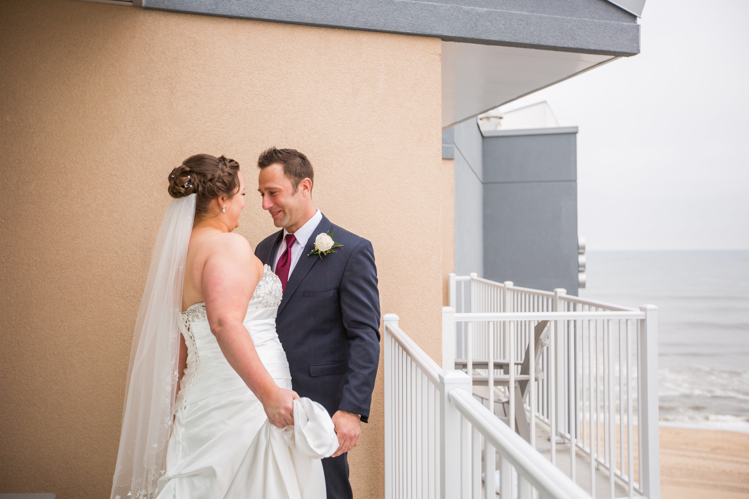 The couple does a first look from the balcony overlooking the Atlantic ocean at the Hyatt in Ocean City.