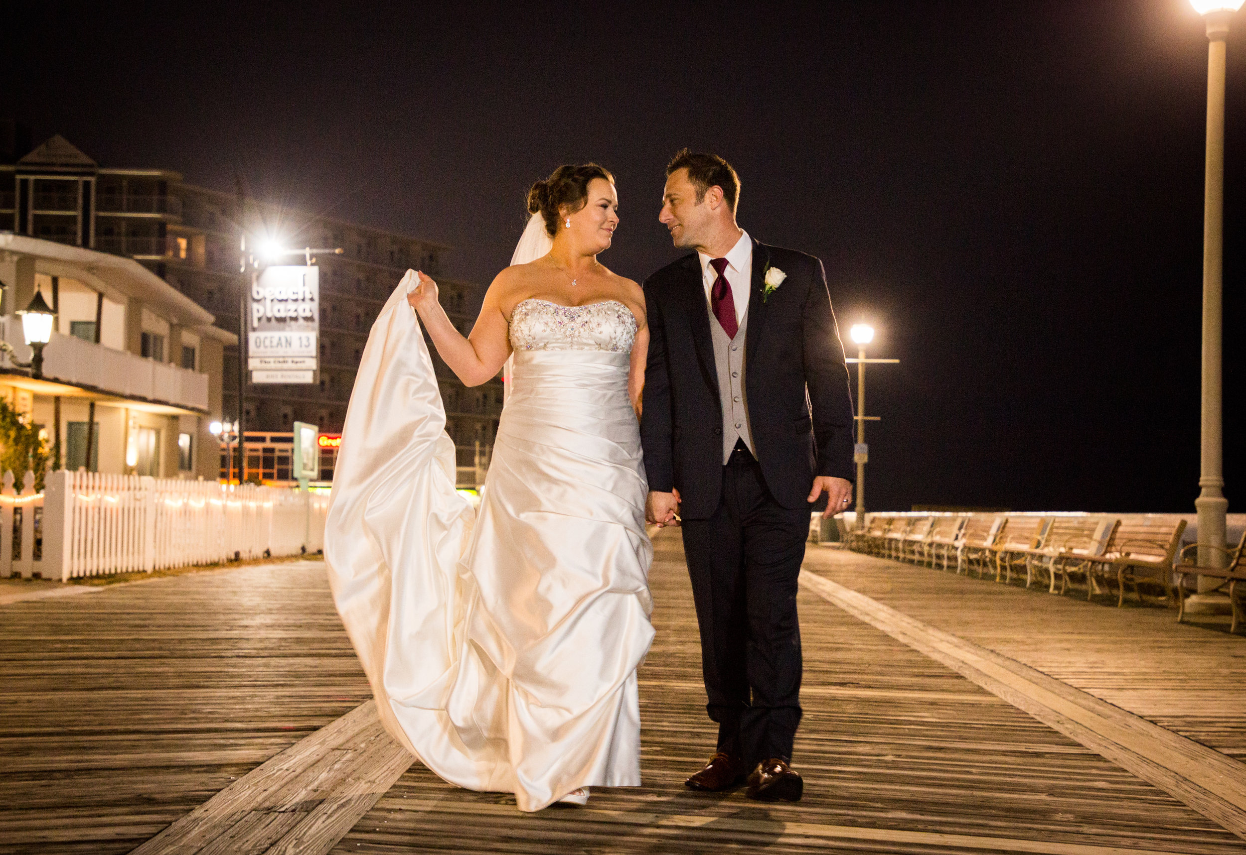 Bride and groom walk down the Ocean City boardwalk at dusk after saying I do.
