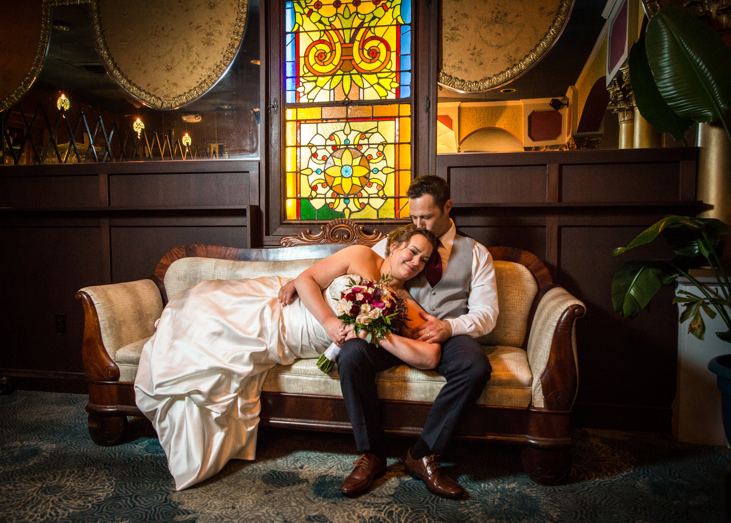 Husband and wife relax together on Victorian couch beneath a beautiful stained glass window in the historic Ocean 13 wedding venue.