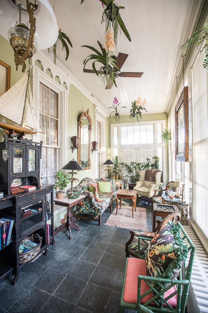 Sun room beautifully staged with furniture and accents indicative of the 18th century.