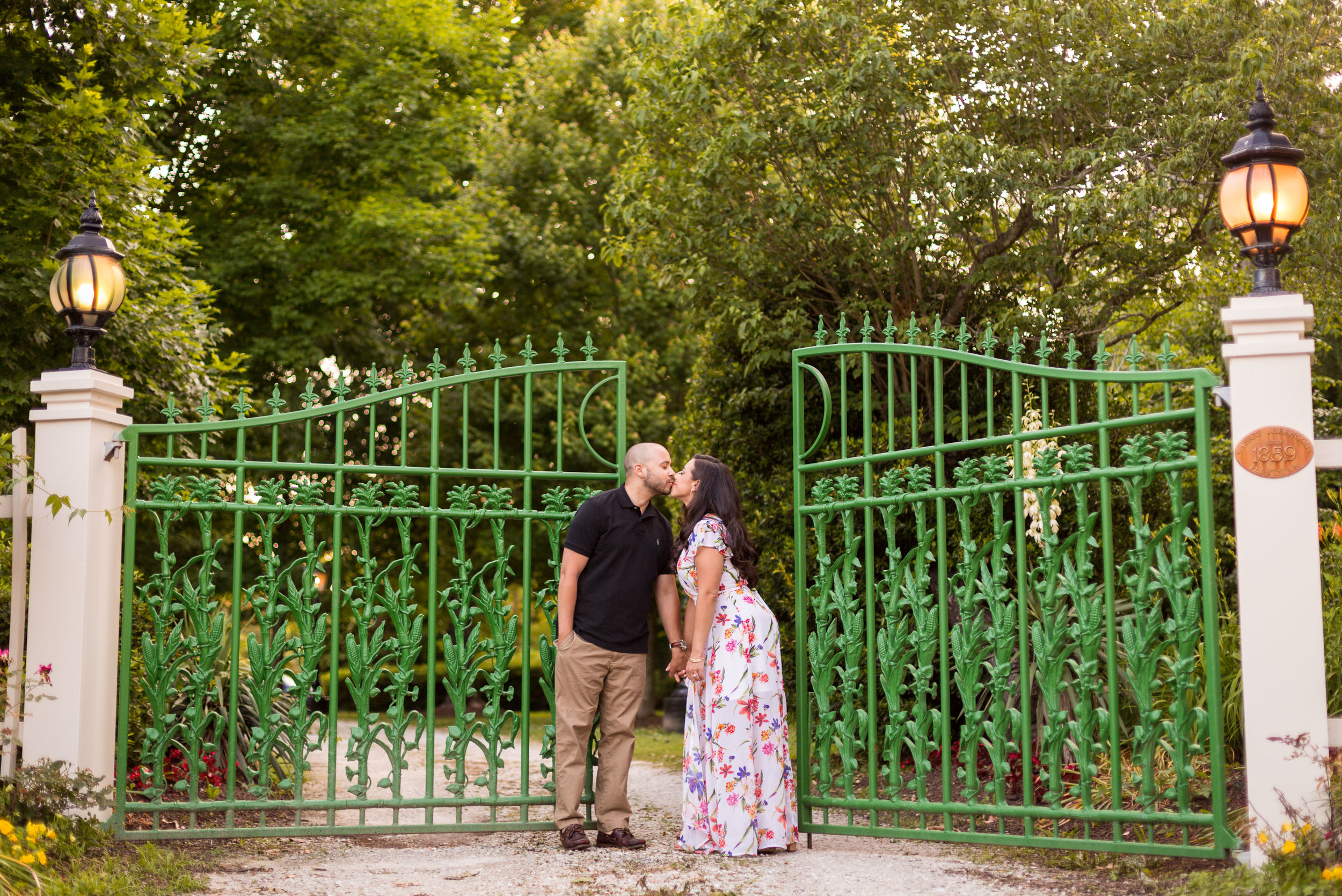 An engaged couple share a kiss in front of the green metal gate leading to the historic Merry Sherwood wedding venue near Ocean City Maryland.
