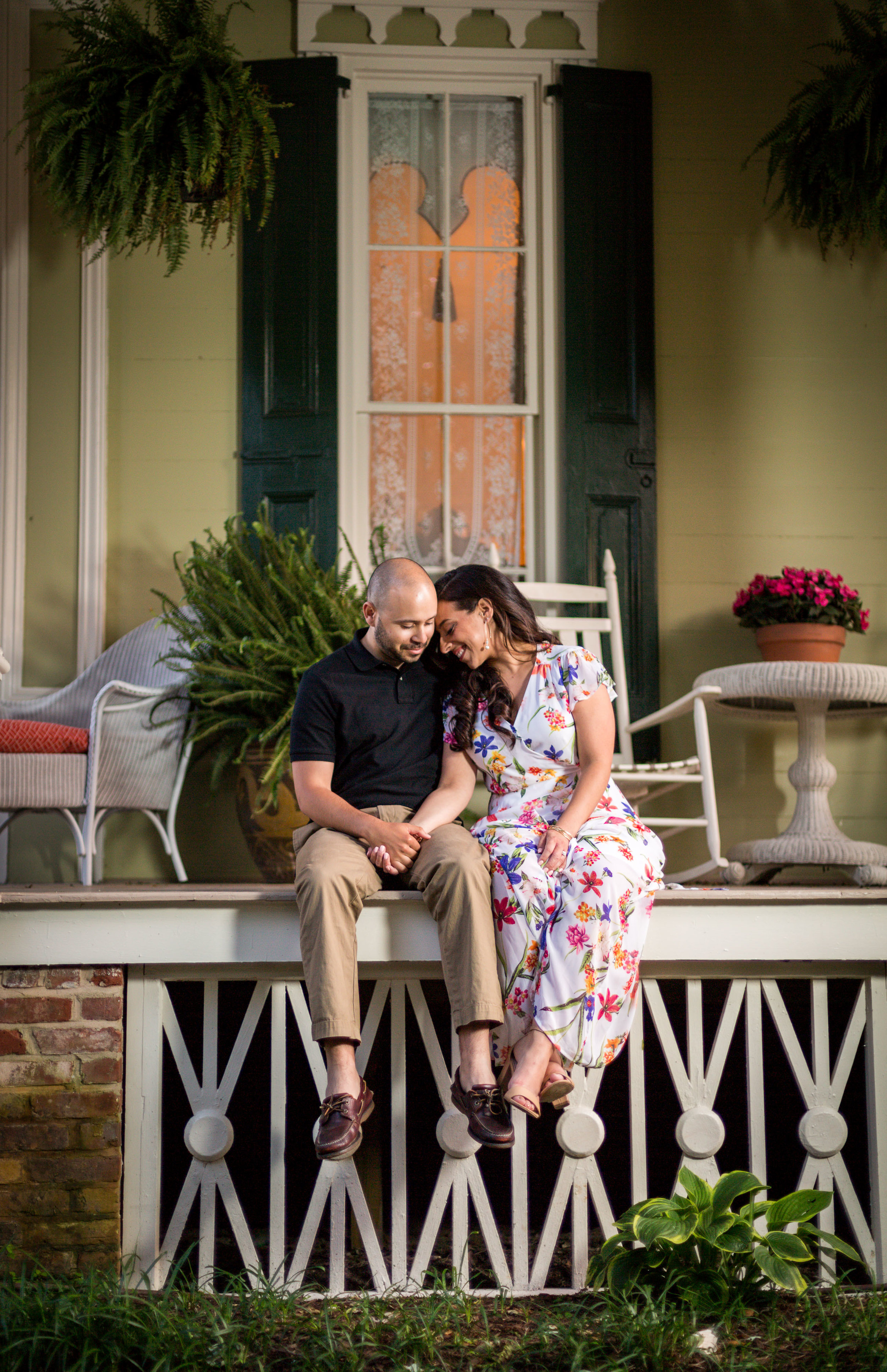 A sweet couple sits on the side porch during their engagement photo session near Ocean City Maryland.