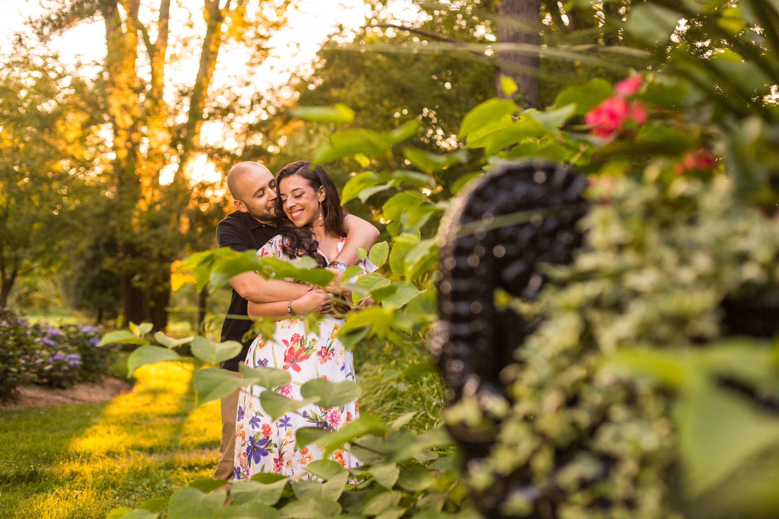 Engaged couple Jairo and Alicia bathe in the glowing sunset in the gardens of Merry Sherwood.