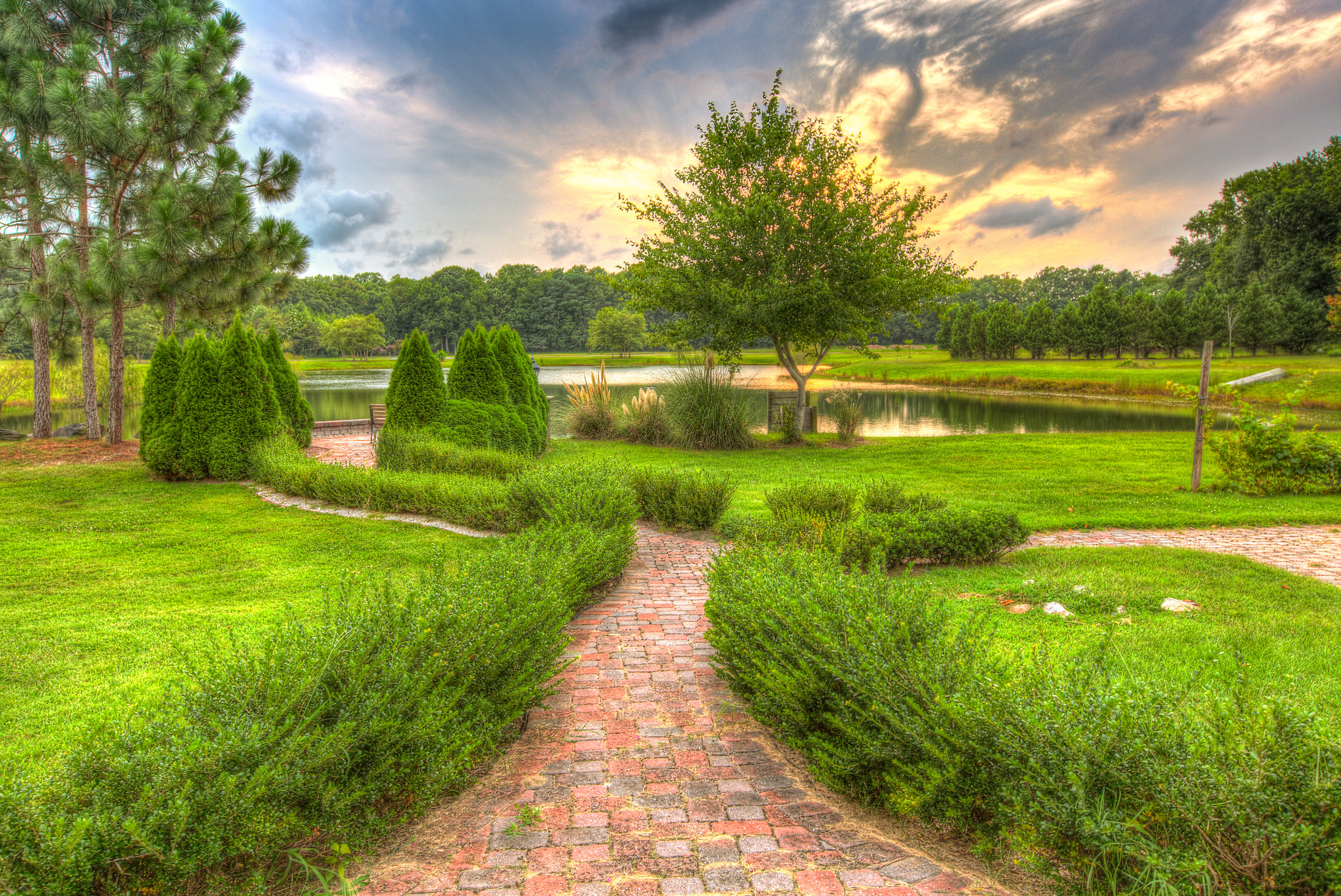 A beautiful brick path leads to the placid lake. This is just one of the gorgeous scenes for your wedding photos at Smokey Hollow barn wedding venue near the Delaware beaches.