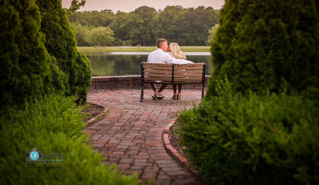 The hedges frame the couple on the bench perfectly during their engagement session at Smokey Hollow in Selbyville, De.