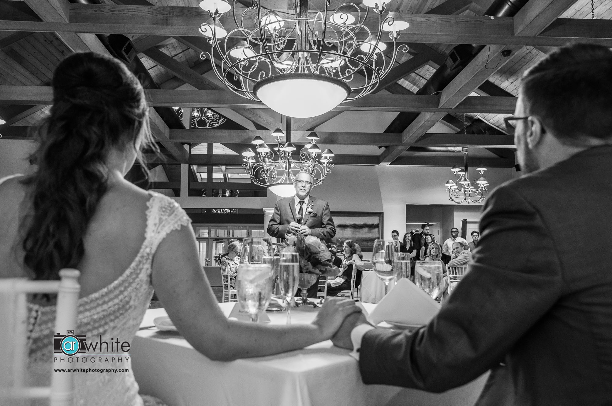 A classic black and white photojournalistic style image of the father of the bride's speech during the wedding reception at Lighthouse Sound.