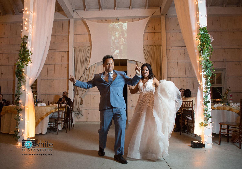 Bride and groom make their grand entrance at Kylan Barn wedding venue.