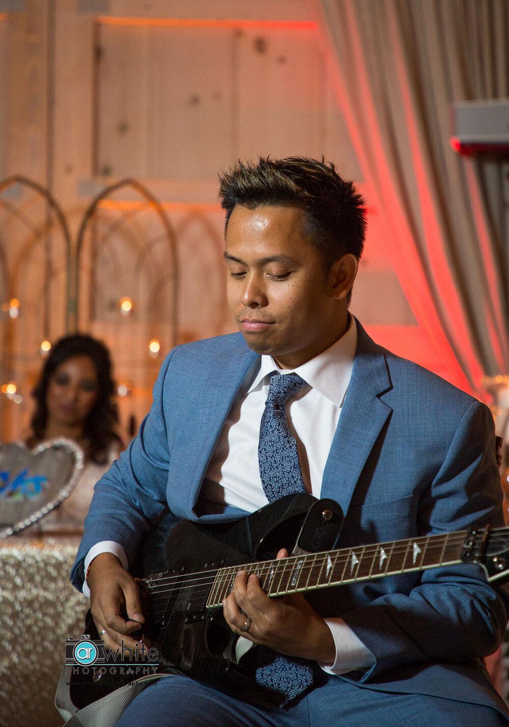 Groom's guitar performance at Kylan Barn wedding reception.