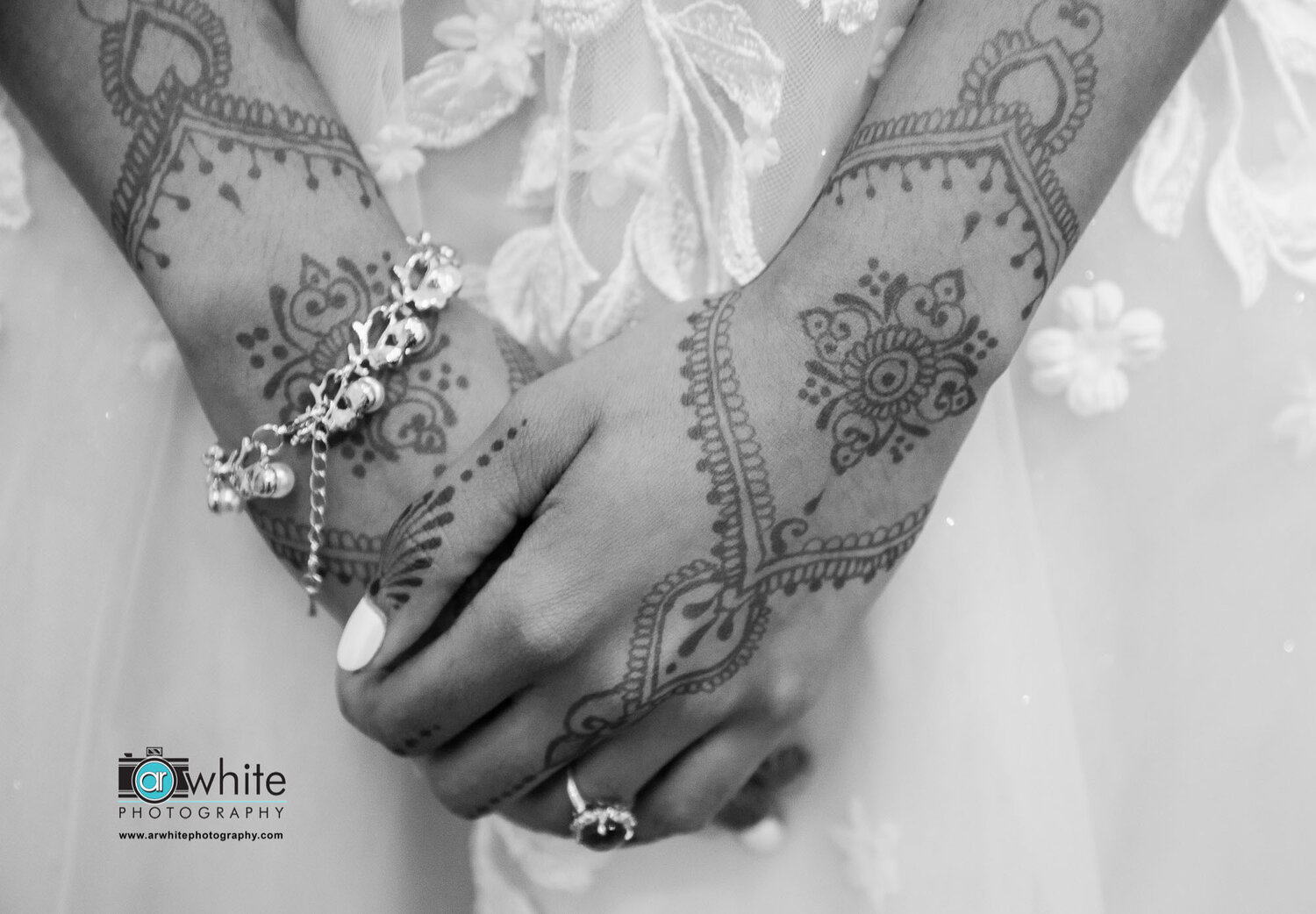 Lovely henna tattoos adorn the bride's hands for her wedding at Kylan Barn.
