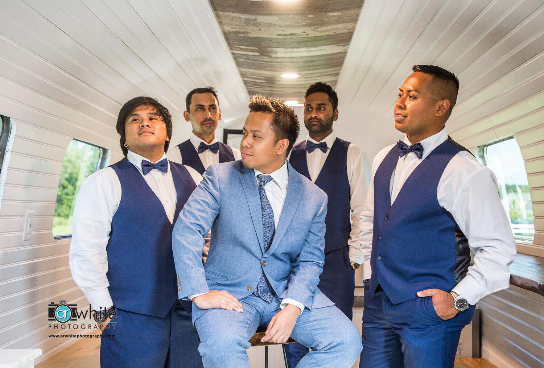 Groom poses with groomsmen at Kylan Barn.