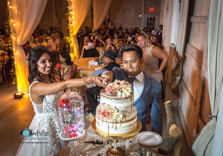Cutting the wedding cake at Kylan Barn wedding.