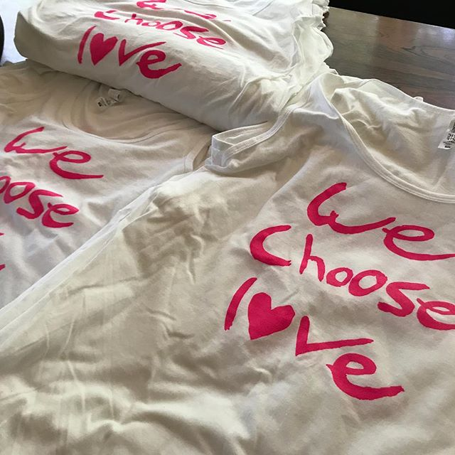We Choose Love shirts ready to go for tomorrow's PAINT THE PARK PINK breast cancer fundraiser at the US Cellular Baseball field with the Medford ROGUES baseball team... YoMIND is co-sponsoring the event with RASA Yoga. These WE Choose L❤VE shirts will be available for purchase with a profits going to support Breast cancer research and to the We Choose love Foundation (in Taliesin Myrddin Namkai-Meche).... choosing love always, for Tilly, and us all.  Come join us for some yoga in the park!! Registration is at 9...class starts at 10.  Cost $5 for class $12 for class AND the baseball game in the evening! #chooselove #breastcancerawareness #kindnessisasuperpower #yomind #yomindmatters #yogaisasuperfood #movewithcommunity #rasayoga #happychemicals #givetoget