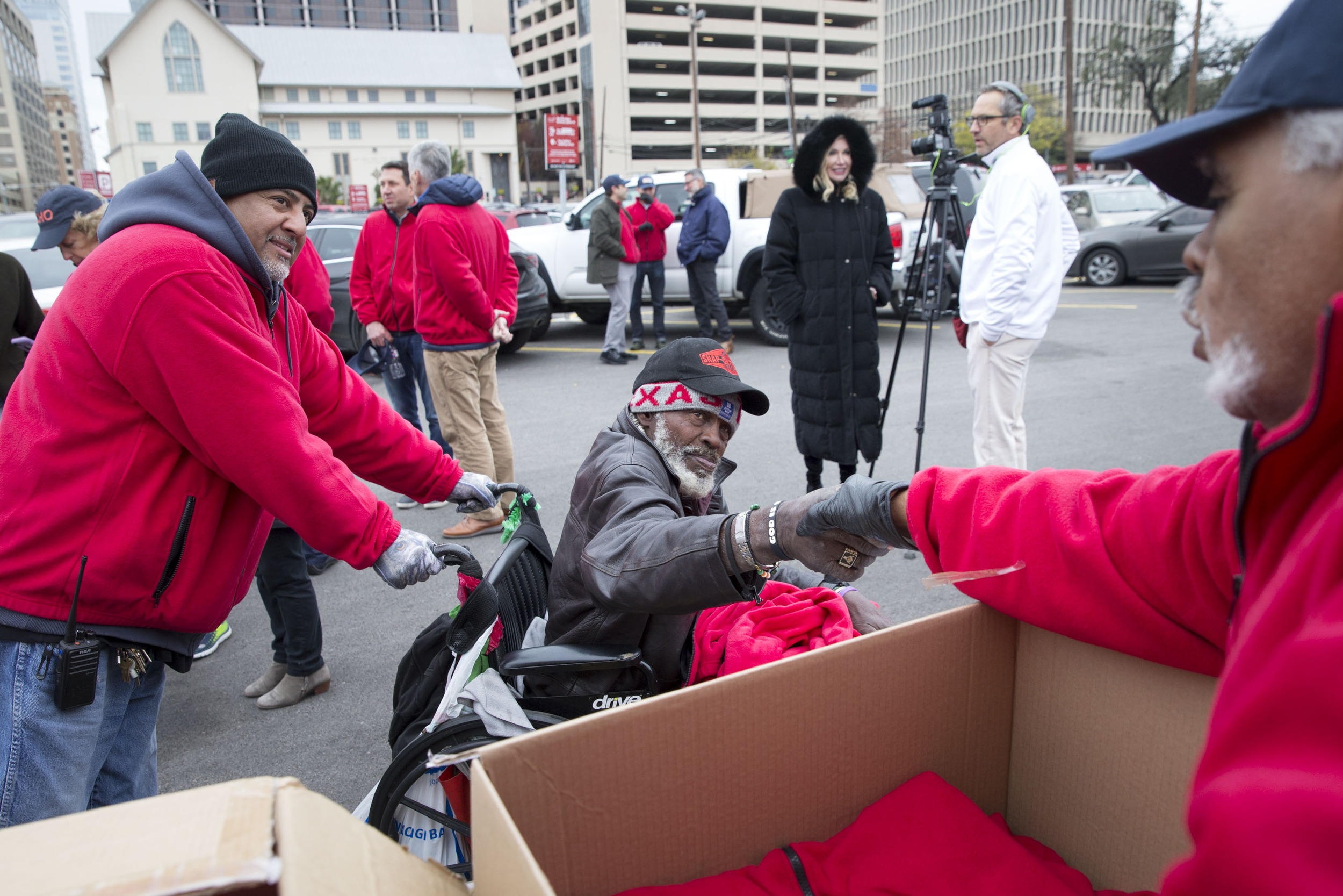 """Purvis Lewis, pushed by Eric Lopez, shakes hands with Manuel Olguin to thank him after receiving a free fleece sweater on Friday, Dec. 14, 2018, as part of the Red Sweater Project. The project, created in partnership between the Cielo Property Group and Livsn Designs, is part of a $1 million commitment to solving homelessness in Austin. According to the city's annual """"Point-In-Time"""" count, at least 2,000 people in Austin currently experience homelessness on any given night."""