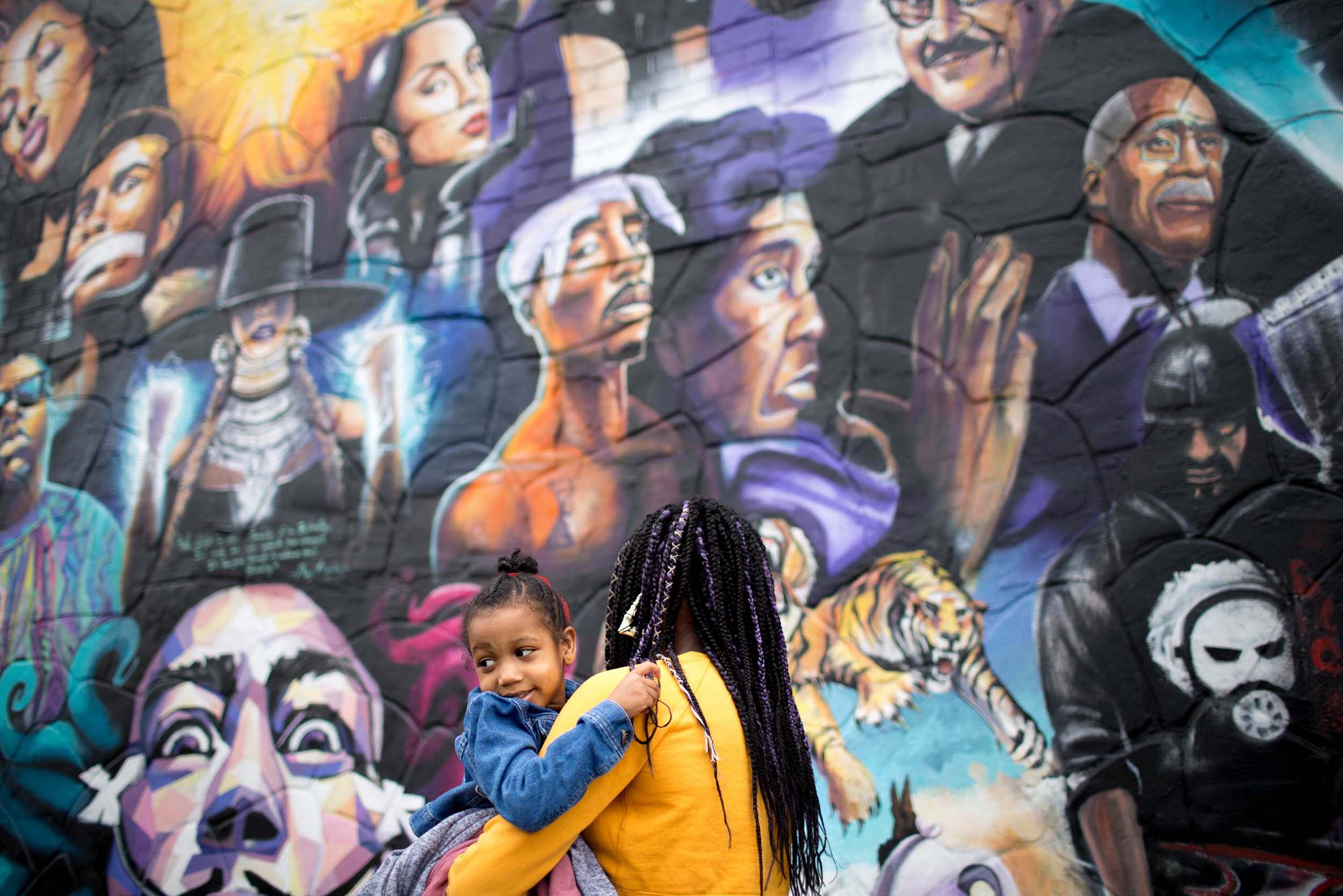 Ayanna Lewis holds a younger relative at the mural unveiling at 12th and Chicon streets in East Austin, Texas, on Feb. 17, 2018. The mural replaced the previous one that honored mostly black musicians after it was painted over by the new owners of the building.