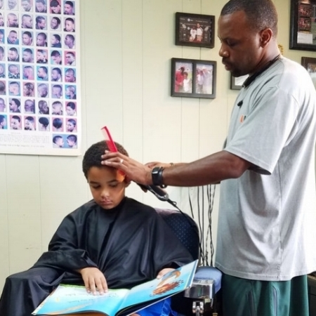 """READING HAIRCUTS    In a small barbershop in Ypsilanti, Michigan, kids pick out a book and head to the chair for their haircuts. That's because children 12 and under who visit The Fuller Cut can get a $2 discount on their $11 haircut for doing a simple task: reading to the barber. Alexander Fuller and barber Ryan Griffin started their  """"Read to your Barber Program""""  more than a year ago. Kids and their parents can't get enough of it.   — Huffpost.com"""