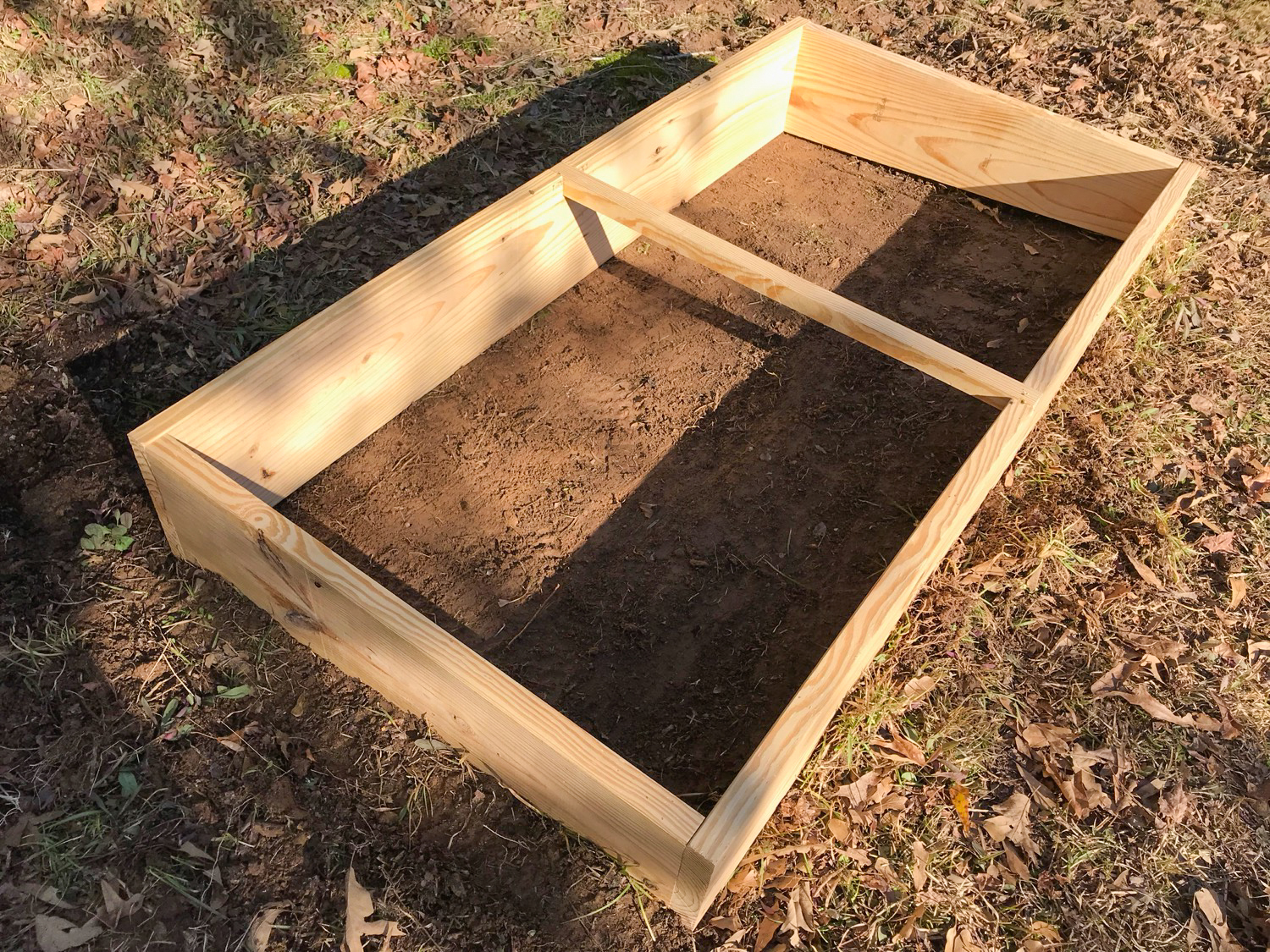 I constructed the box out of two ten-foot long 2 × 12's cut into two pieces—6 ft long for the front and back and 3 ft long for the sides. To create a slope on the top of the box to maximize sun exposure, I cut 4 in off one of the 6 ft boards to make it 8 in tall, and for the side boards, I cut a slant (1.3 in drop per 1 ft board length). Once constructed on the ground, the cold frame is turned over so that the front and back boards have a slight slant in one direction and so that the top is flush with the light. Notches made in the middle front and back allow the installation of a support beam.