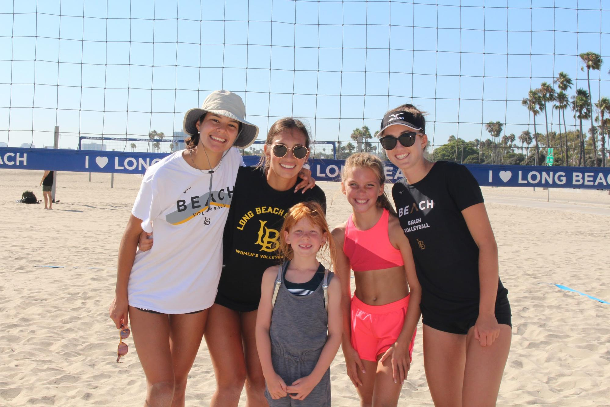 Two of the kids who participated in the volleyball clinic pictured along with student-athletes who helped lead the clinic.