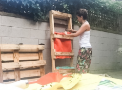 Maria with recycled coffee bags and pallets making a garden