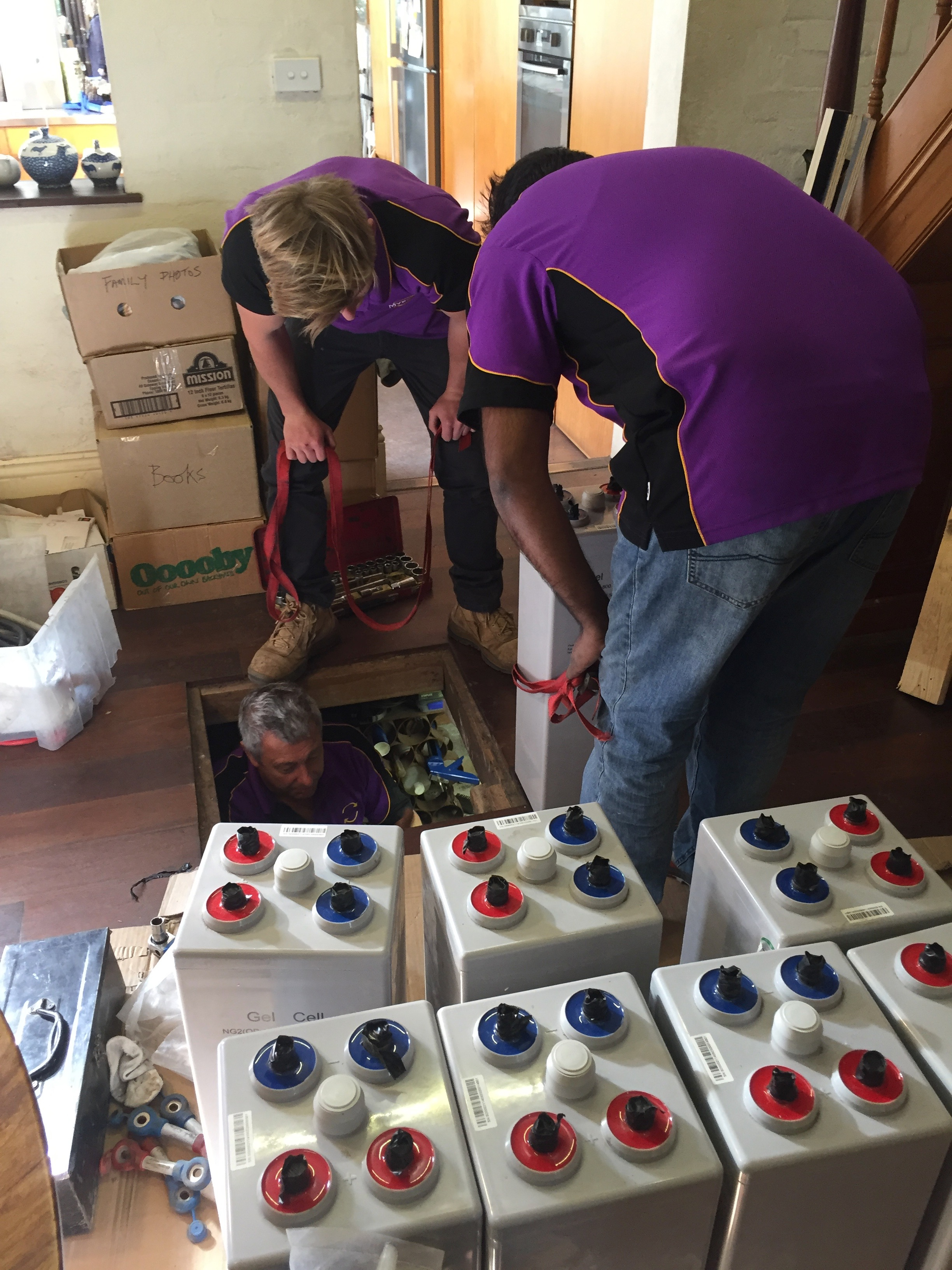 • Gel batteries on dining room floor with MV Solar workers lowering batteries to Michael in the cellar